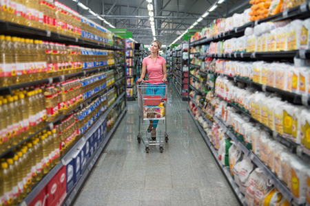 intolerancia: Shopping Woman Looking at the Shelves in the Supermarket - Portrait of a Young Girl in a Market Store With a Shopping Cart