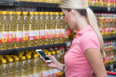 Young Woman Shopping in Supermarket While Using Smartphone in Store Stock Photo
