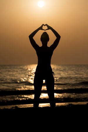 under heart: Beautiful Female Model Enjoying Sunset and Making Heart Sign on Sun at Seaside - Calm Water Reflects Silhouette of Woman - Sun Goes Under Horizon