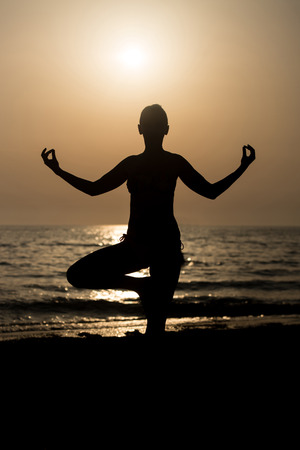 siluet: Young Healthy Woman Practicing Yoga Fitness Exercise on the Beach at Sunset - Healthy Lifestyle Concept - Copy Space Text
