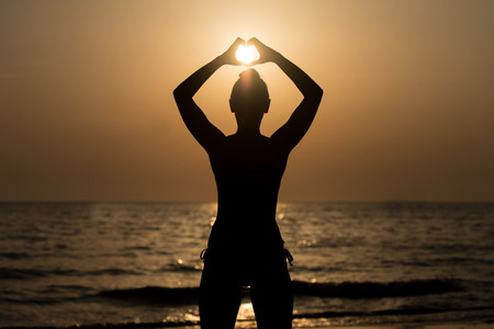 Beautiful Female Model Enjoying Sunset and Making Heart Sign on Sun at Seaside - Calm Water Reflects Silhouette of Woman - Sun Goes Under Horizon