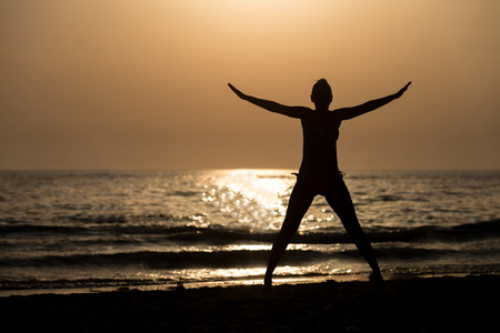 siluet: Silhouette of Woman With Raised Hands And Jumping Around on the Beach at Sunset - Copy Space Text
