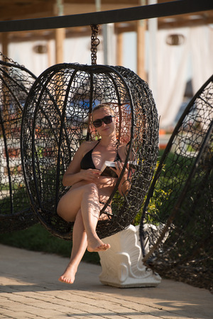 Young Woman Sitting in a Metal Rattan Hanging Basket With Cushions - Enjoying the Sunny Day in an Outdoor Reading a Book by the Sea Stock Photo