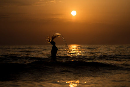siluet: Girl Throwing Water With Her Wet Hair in the Ocean During Sunset - Copy Space Text Stock Photo