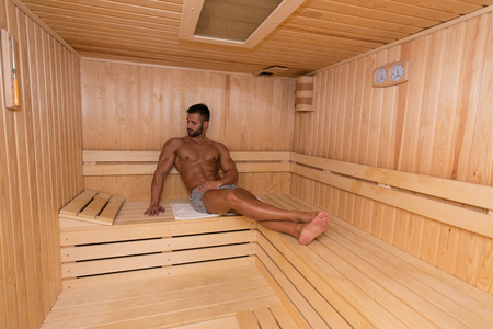 sauna nackt: Happy Good Looking And Attractive Young Man With Muscular Body Relaxing In Hot Sauna Lizenzfreie Bilder
