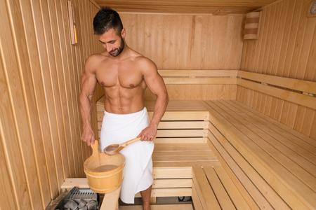 Glücklich gut aussehend und attraktive junge Mann mit dem muskulösen Körper gießt Wasser auf Hot Rocks In Sauna