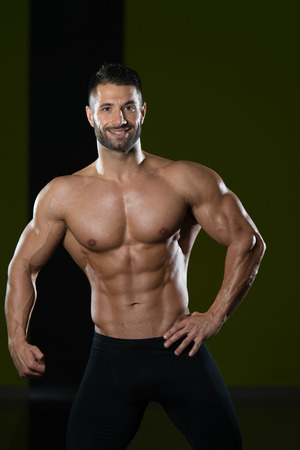 Handsome Man Standing Strong In The Gym And Flexing Muscles - Muscular Athletic Bodybuilder Fitness Model Posing After Exercises Stock Photo