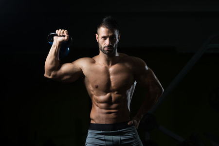flexing: Healthy Man Exercising With Kettle Bell And Flexing Muscles - Muscular Athletic Bodybuilder Fitness Model Exercises