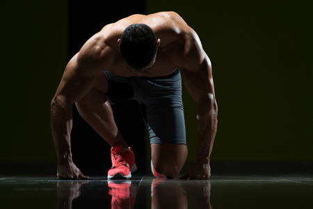 starting position: Strong Muscular Men Kneeling On The Floor - Almost Like Sprinter Starting Position Stock Photo