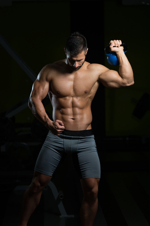 Young Man Working Out With Kettle Bell In A Dark Gym - Bodybuilder Doing Heavy Weight Exercise With Kettle-bell
