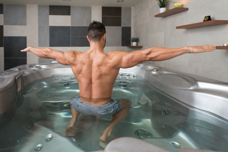 water hottub: Wellness Spa - Man Flexing Muscles in Hot Tub Whirlpool Jacuzzi Indoors at Luxury Resort Spa Retreat - Handsome Young Male Model Standing Strong in Water Near Pool on Travel Vacation Holiday