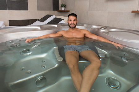 water hottub: Wellness Spa - Man Relaxing in Hot Tub Whirlpool Jacuzzi Indoors at Luxury Resort Spa Retreat - Handsome Young Male Model Relaxed Resting in Water Near Pool on Travel Vacation Holiday