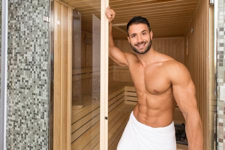 Glücklich gut aussehend und attraktive junge Mann mit dem muskulösen Körper Entspannung im Hot Sauna