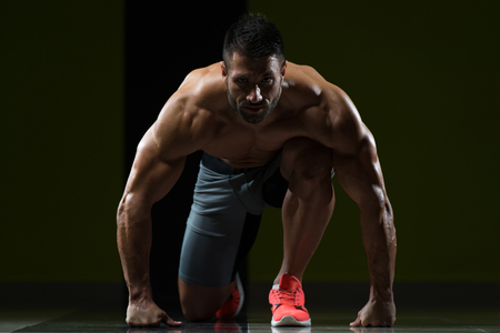Strong Muscular Men Kneeling On The Floor - Almost Like Sprinter Starting Position Stock Photo