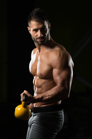 Healthy Man Exercising With Kettle Bell And Flexing Muscles - Muscular Athletic Bodybuilder Fitness Model Exercises