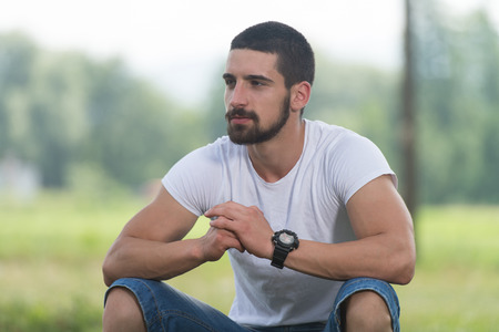 repose: Portrait Of A Young Man Sitting on Grass - Handsome Guy Repose in Nature - Outdoors - Outside