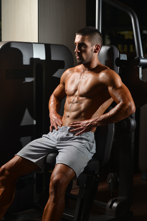 muscled: Resting Time - Confident Muscled Young Man Resting In Healthy Club Gym After Exercising
