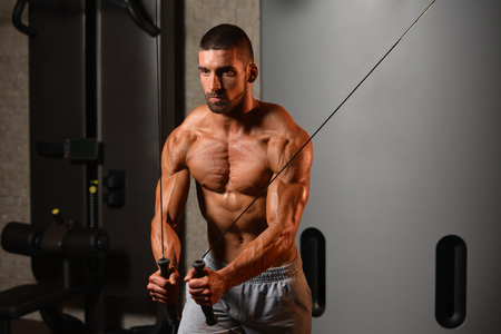 strenght: Young Man Is Working On His Chest With Cable Crossover In A Modern Fitness Gym Stock Photo