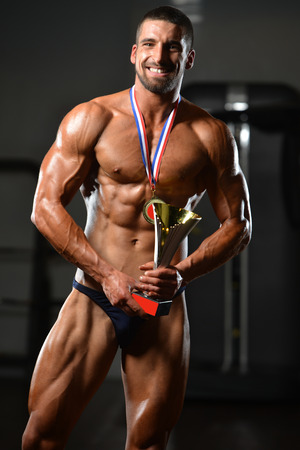 Bodybuilder Competitor Showing His Winning Medal - Male Fitness Competitor Showing His Winning Medal Stock Photo