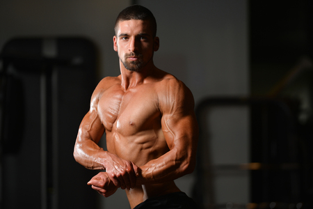 flexing: Portrait Of A Young Physically Fit Man Showing His Well Trained Body - Muscular Athletic Bodybuilder Fitness Model Posing After Exercises Stock Photo