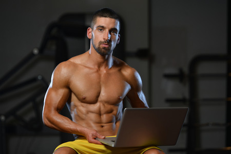 muscled: Resting Time - Confident Muscled Young Man Resting In Healthy Club Gym And Using Laptop