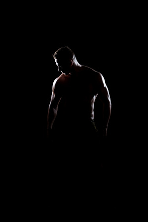 Silhouette Portrait Of A Young Physically Fit Man Showing His Well Trained Body - Muscular Athletic Bodybuilder Fitness Model Posing After Exercises Stock Photo