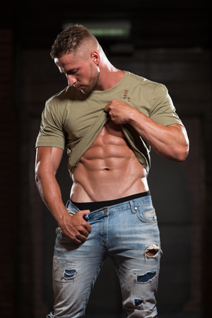 Handsome Young Man In Jeans & T-shirt Standing Strong In The Gym And Flexing Muscles - Muscular Athletic Bodybuilder Fitness Model Posing After Exercises