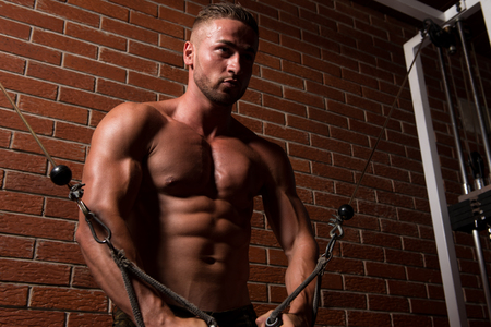 Young Bodybuilder Is Working On His Chest With Cable Crossover In Gym Stock Photo