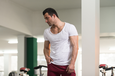 iron man: Healthy Young Man in White T-shirt Standing Strong and Flexing Muscles - Muscular Athletic Bodybuilder Fitness Model Posing After Exercises Stock Photo