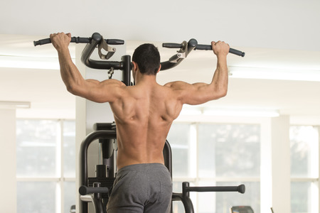 Young Man Athlete Doing Pull Ups - Chin-Ups In The Gym Stock Photo