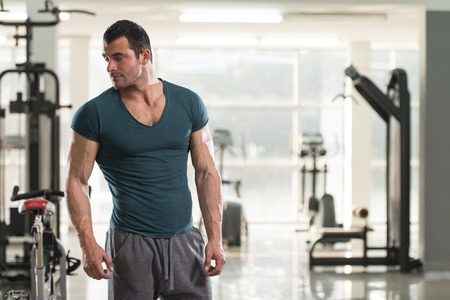 Portrait of a Young Physically Fit Man in Green T-shirt Showing His Well Trained Body - Muscular Athletic Bodybuilder Fitness Model Posing After Exercises