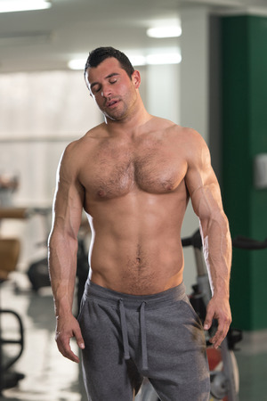 Portrait of a Tired Muscular Man Standing in Health Club Standard-Bild