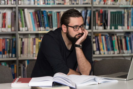 Sleeping Caucasian Student Sitting And Leaning On Pile Of Books In College - Shallow Depth Of Field
