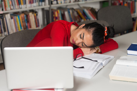Sleeping Woman Student Sitting And Leaning On Pile Of Books In College - Shallow Depth Of Field Stock Photo