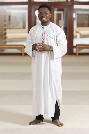 religious clothing: Portrait Of A African Muslim Man Making Traditional Prayer To God While Wearing A Traditional Cap Dishdasha Stock Photo