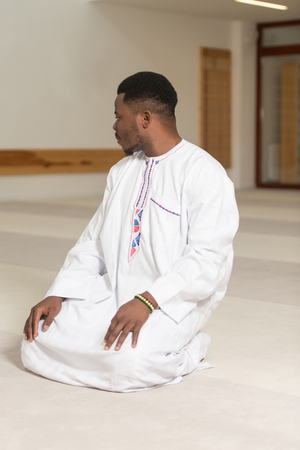 African Muslim Man Making Traditional Prayer To God While Wearing A Traditional Cap Dishdasha