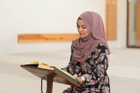 Muslim Woman Making Traditional Prayer To God While Reading The Quran In Mosque
