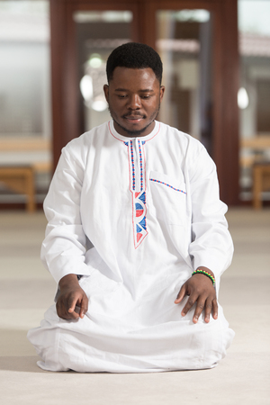 religious clothing: African Muslim Man Making Traditional Prayer To God While Wearing A Traditional Cap Dishdasha