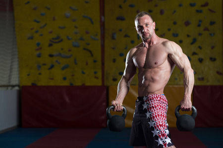 kettle bell: Man Working Out With Kettle Bell In A Gym - Bodybuilder Doing Heavy Weight Exercise With Kettle-bell Stock Photo