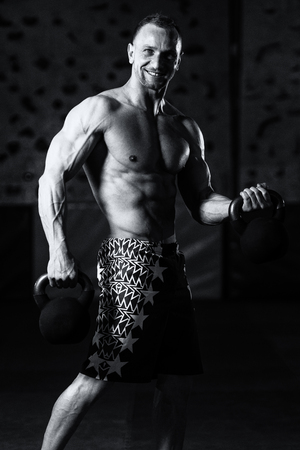 kettle bell: Man Exercising With Kettle Bell And Flexing Muscles - Muscular Athletic Bodybuilder Fitness Model Exercises Stock Photo