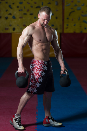 Man Working Out With Kettle Bell In A Gym - Bodybuilder Doing Heavy Weight Exercise With Kettle-bell Stock Photo