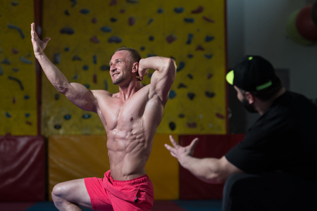 corrects: Portrait Of A Man Posing Bodybuilding Poses In Fitness Center and Personal Trainer Corrects Him Stock Photo