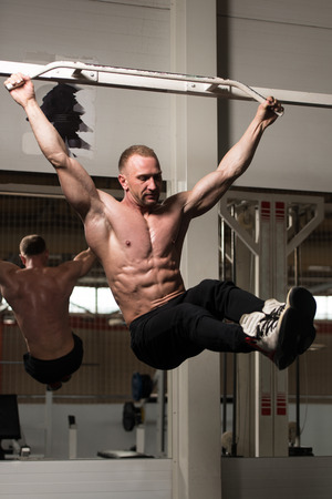 physique: Man Performing Hanging Leg Raises Exercise - One Of The Most Effective Ab Exercises Stock Photo