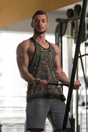 physique: Muscular Fitness Bodybuilder Doing Heavy Weight Exercise For Biceps On Machine With Cable In The Gym