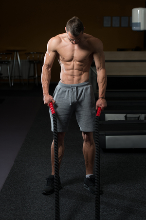 battling: Battling Ropes Young Man At Gym Workout Exercise Stock Photo