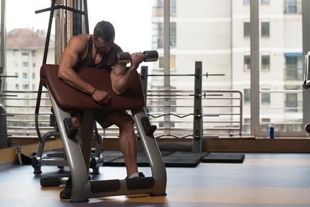 physique: Man Working Out Biceps In A Gym - Dumbbell Concentration Curls