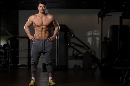 그의 잘 훈련 된 몸 - 근육 운동 애호가 휘트니스 모델 포즈를 보여주는 젊은 신체적으로 적합 한 남자의 초상화 운동 후