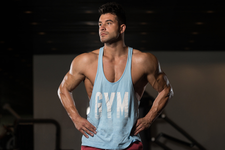 physically fit: Portrait Of A Young Physically Fit Man In Blue Undershirt Showing His Well Trained Body - Muscular Athletic Bodybuilder Fitness Model Posing After Exercises Stock Photo