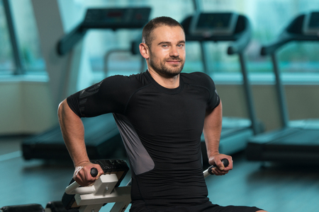 Young Fitness Man Working Out Triceps On Roman Chair In Fitness Center Stock Photo