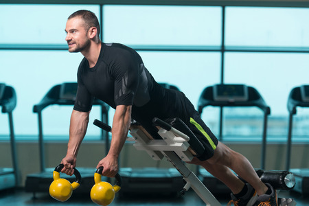 kettle bell: Fitness Man Working With Kettle Bell In A Gym - Kettle-bell Exercise
